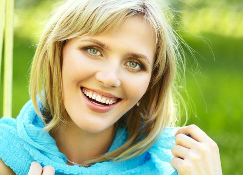 woman with perfect teeth relaxing and smiling outside