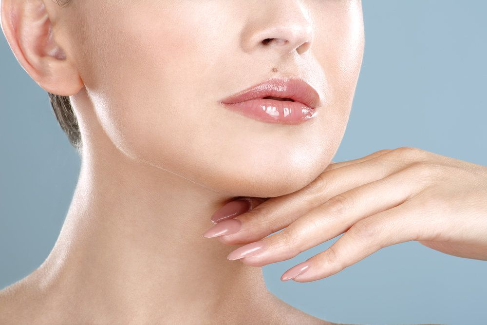 Attractive woman with plump lips holding hand under chin