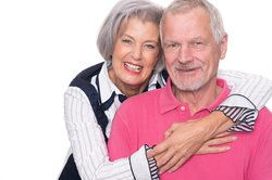 Senior couple smiling, in front of white background.