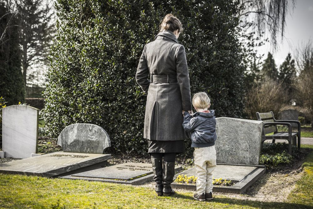 A mother and child visiting the grave of the deceased patriarch of the family, who died in a construction accident