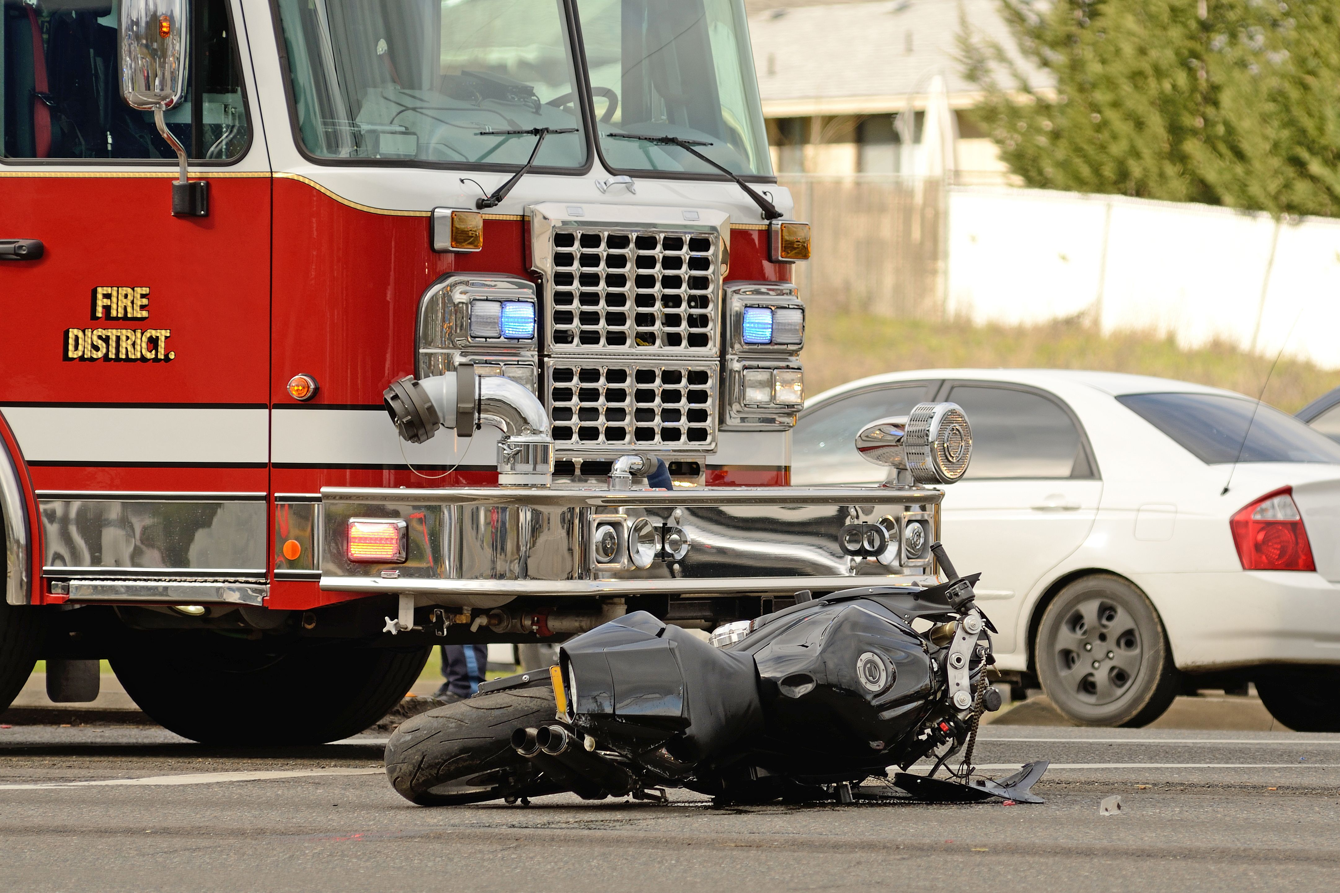 A motorcycle in front of a fire engine after an accident