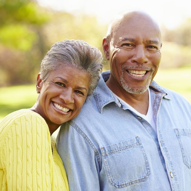 An attractive elderly couple smiles while standing outside.