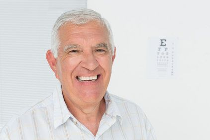 Smiling elderly man with white hair and healthy teeth
