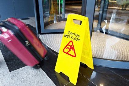 Wet floor sign and suitcase next to revolving door