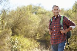 Smiling man wearing plaid shirt hiking and wearing backpack