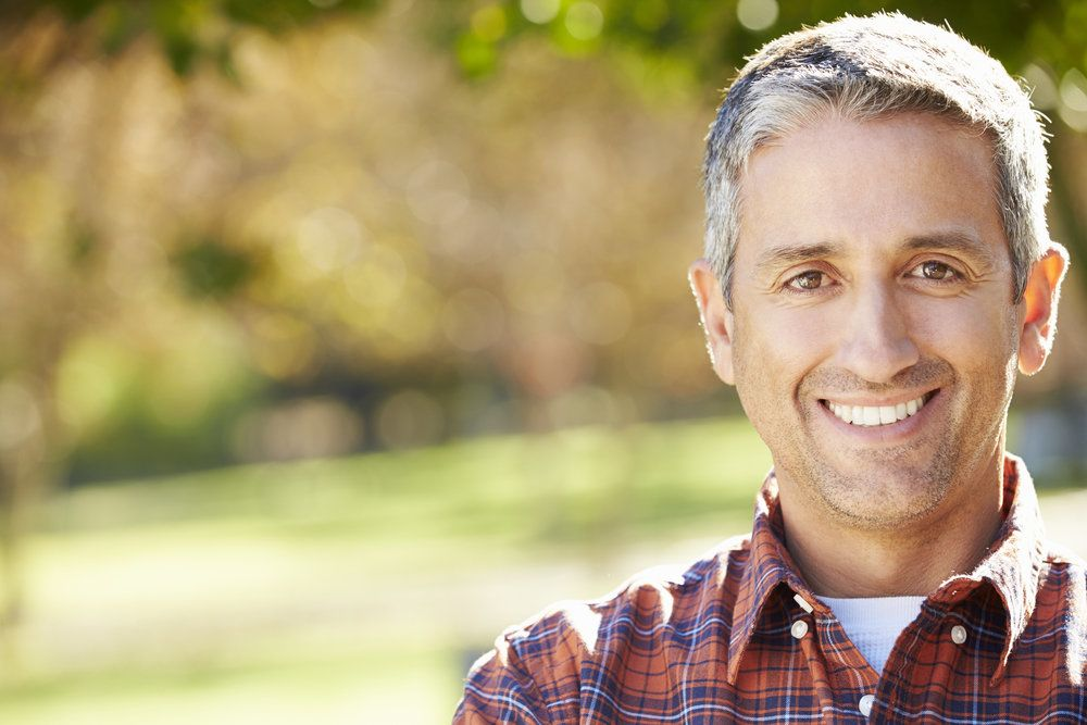 A grey-haired man in a plaid shirt smiling outdoors