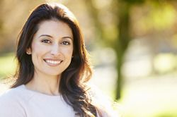 A woman with long dark hair and a beige light sweater stands outside in a park and smiles confidently in the sunlight