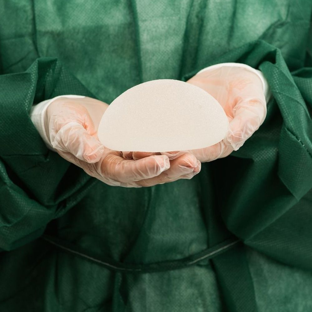 A surgeon holding a breast implant