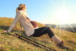 Very pregnant woman relaxing during hike on a grassy hill