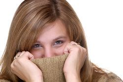 A woman covering her mouth with her shirt