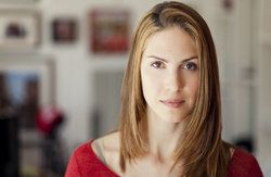 Stoic woman with long brown hair wearing red sweater