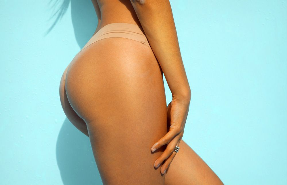 Woman's tan, round butt in nude thong