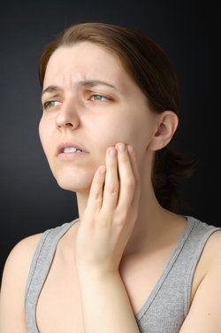 A woman suffers from a painful toothache