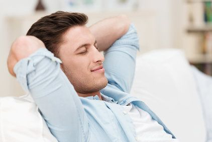 A man relaxing with his hands behind his head.