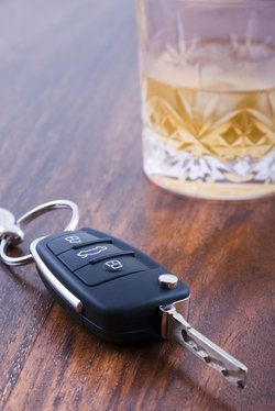 A car key lying beside a glass of liquor