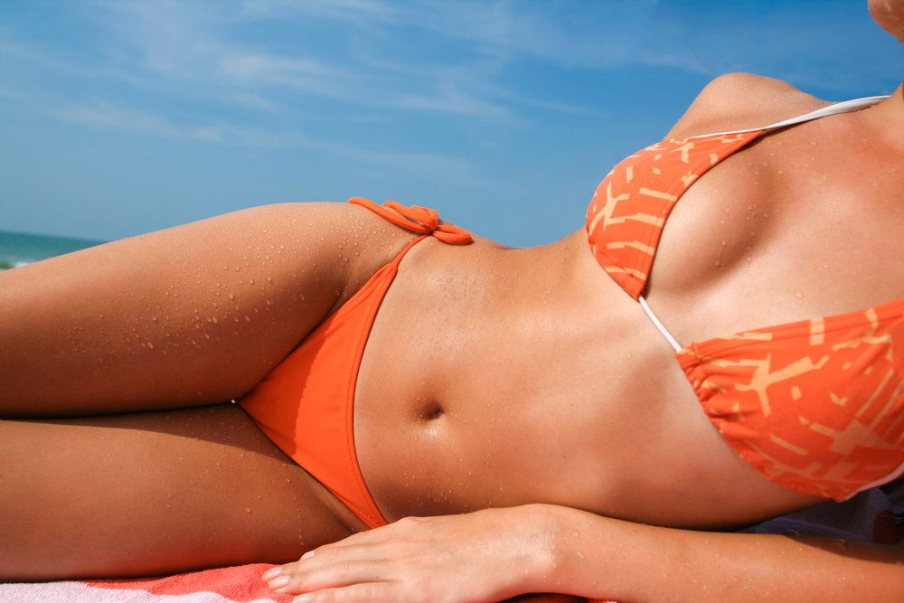 A woman in an orange bikini on the beach