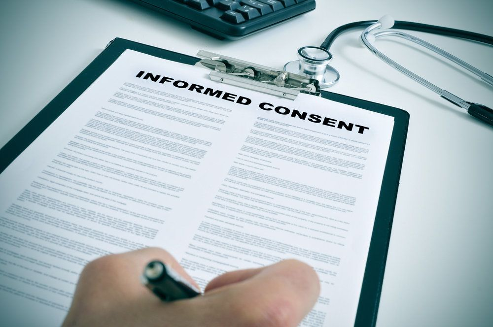 A patient signing an informed consent form