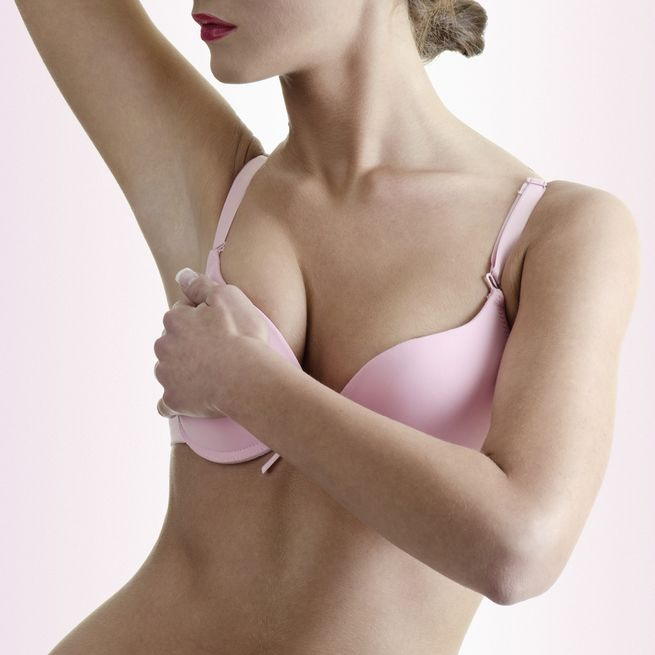 Woman in pink bra, cupping right breast