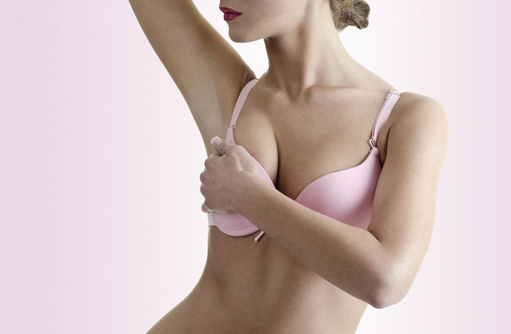 Woman in pink bra raising arm and holding breast