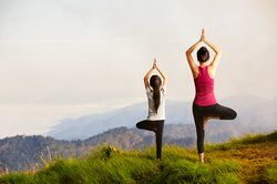 Two women holding yoga poses on picturesque grassy mountaintop