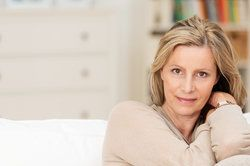 Attractive middle-aged woman sitting on couch with arms near face