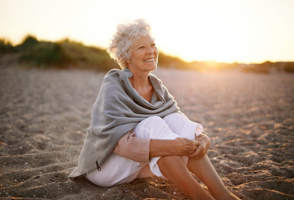 Elderly woman with short grey hair sitting on a sandy beach smiling during twilight.