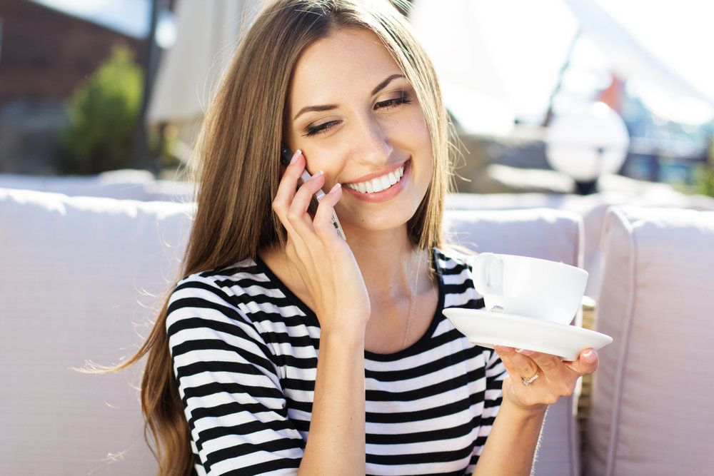 A woman with bright, white, healthy teeth, talking on the phone and holding a coffee cup