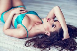 Seductive woman wearing turquoise lingerie lying on back and running hands through hair