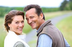A middle-aged couple in a field looking at the camera and smiling.