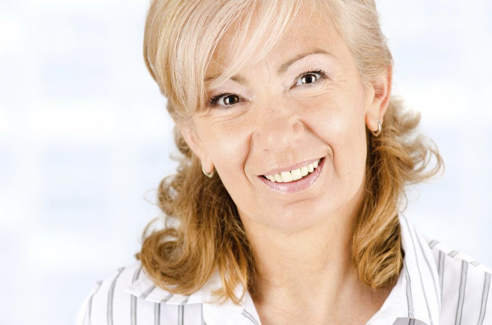 Smiling middle-aged woman with blond hair pulled halfway up