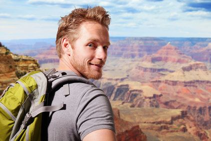 A man looking over his shoulder while standing in front of the Grand Canyon.