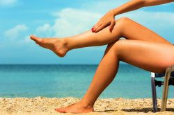 Woman's tan, smooth, fit legs on the beach.
