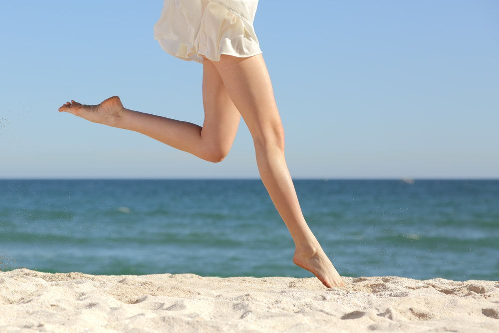 A slim, toned pair of legs running on the beach