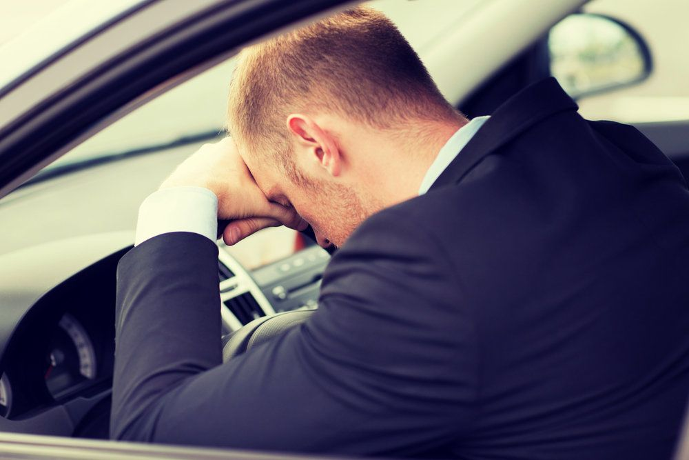 A man with his head on his steering wheel after being pulled over for DUI