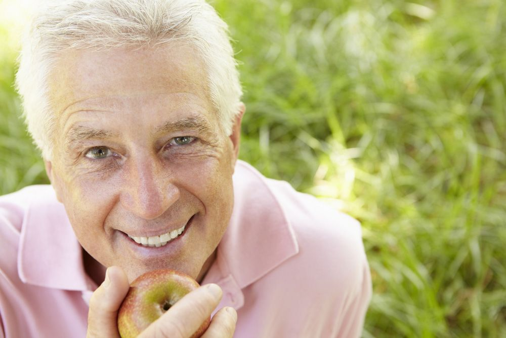 A senior man poised to bite an apple with his healthy teeth