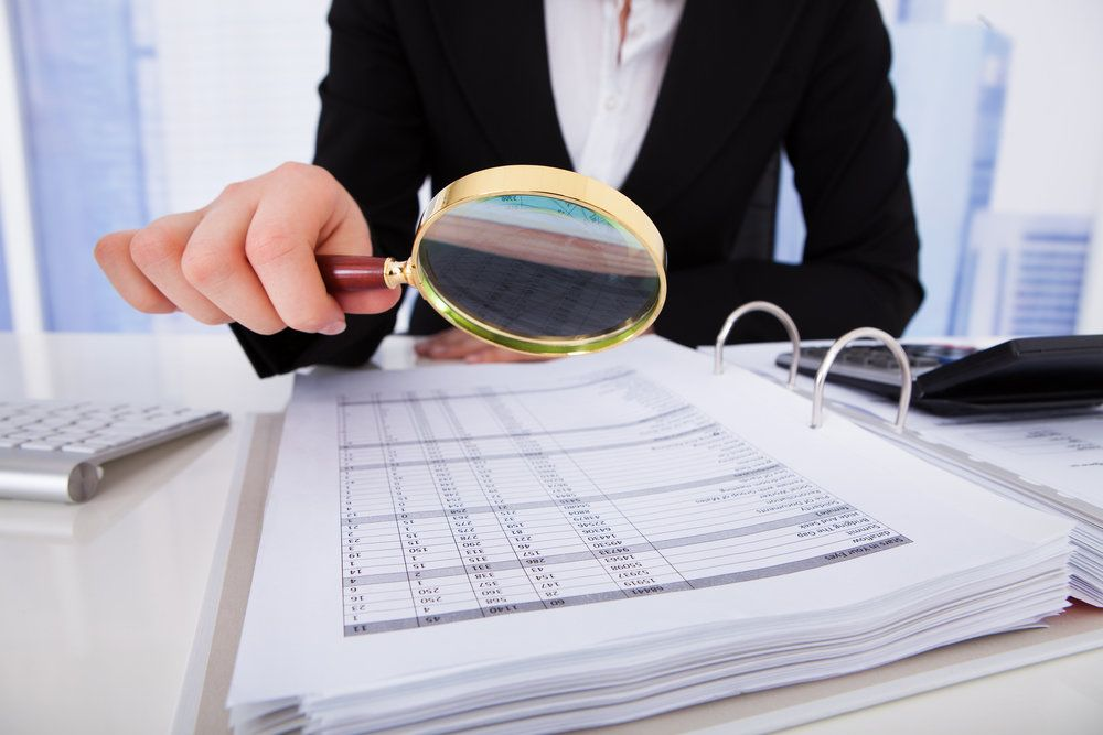 A personal injury attorney scrutinizing numbers with a magnifying glass