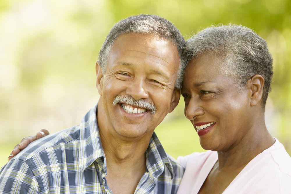 An older couple with healthy looking teeth, smiling