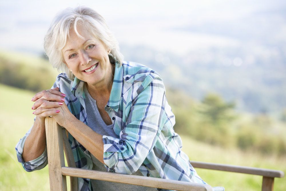 A senior woman sitting outside on a bench and smiling