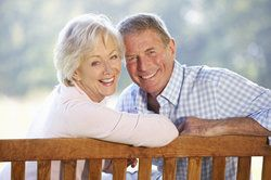 An elderly couple sitting on a bench, flashing their healthy, happy smiles after full mouth reconstruction