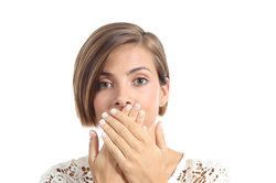 A woman holding her hands over her mouth to conceal her bad breath