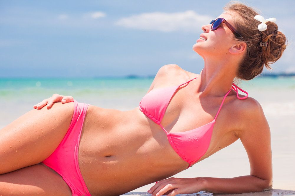 Beautiful woman on the beach, pink bikini