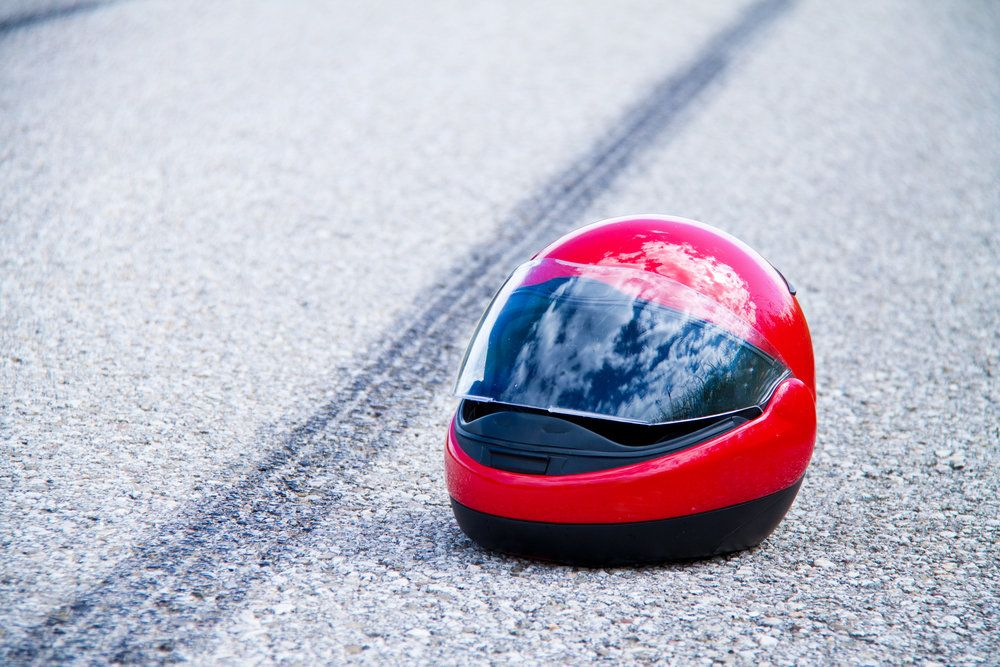 A motorcycle helmet lying on the road next to a skid mark in the aftermath of a motorcycle accident