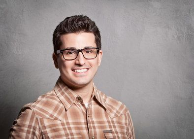 A man wearing a brown plaid shirt with brown hair and glasses.