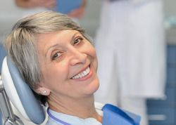 A grey-haired woman sitting in the dentist's chair.