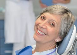 An older woman smiling during a dental visit