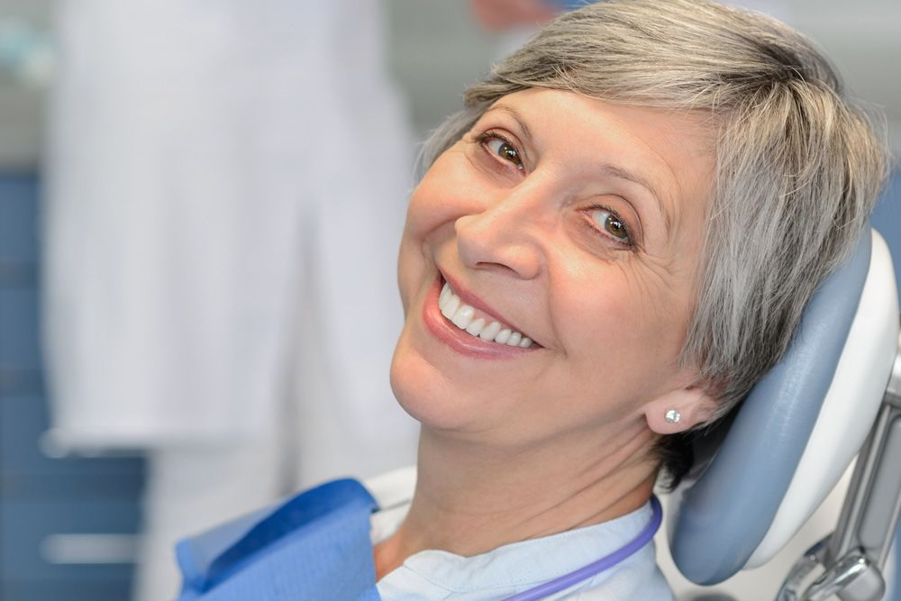 A senior dental patient, smiling as she prepares to undergo treatment