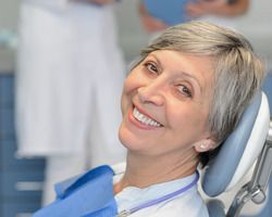 A mature woman with short gray hair reclines in a dental chair, tilting her head to the side and smiling cheerfully