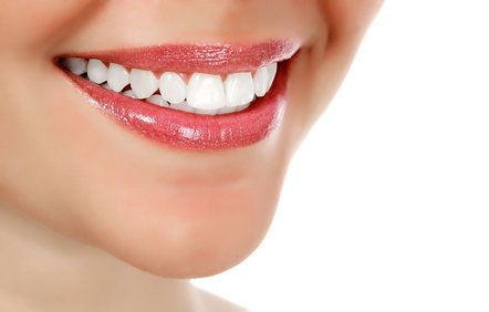 Close up of woman's white teeth and glossy lips