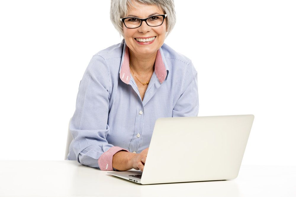 A smiling woman using a laptop computer after successful laser cataract surgery