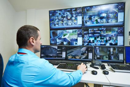 Man viewing footage from multiple surveillance cameras